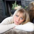 Portrait of good-looking young blonde in chalet with face resting in arms — Stock Photo #9822402
