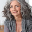 Grey-haired lady sat at home alone — Stock Photo