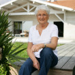 Senior woman sitting in her garden — Stock Photo