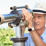 Senior man looking through a telescope — Stock Photo