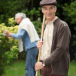 Stock Photo: Senior couple raking leaves in garden