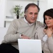 Mature couple on a sofa with laptop computer — Stock Photo