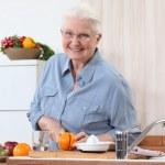 Elderly lady cutting an orange — Stock Photo #9825049