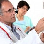 Doctor and nurse preparing IV drip — Stock Photo