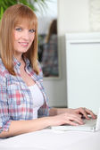 Red-haired woman at computer — Stock Photo