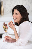 Woman eating chocolate egg — Stock Photo