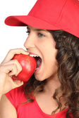 Brunette in red cap biting into apple — Stock Photo