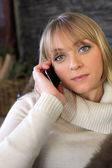 Blond woman making phone call whilst sat on cosy sofa — Stock Photo