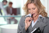 Pensive blond businesswoman chewing on pen — Stock Photo