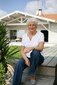 Senior woman sitting in her garden — Stock Photo