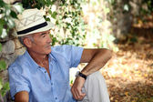 Elderly man sitting against the stone wall — Stock Photo