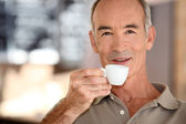 Elderly man drinking coffee — Stock Photo