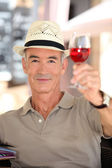 Elderly man toasting with glass of rose wine — Stock Photo