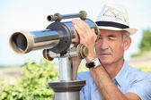 Senior man looking through a telescope — Stock Photo