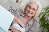Elderly lady shopping on-line — Stock Photo