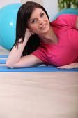 Woman laying on gym mat — Stock Photo