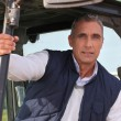 Farmer sat in his tractor - Stock Photo