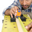 Carpenter measuring a piece of wood — Stock Photo