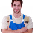 Young decorator holding two different paintbrushes — Stock Photo