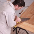 Man sawing plank of parquet — Stock Photo #9955911