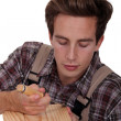 Stock Photo: Carpenter using chisel to sculpt wood