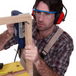 A male carpenter using a jigsaw. - Stock Photo