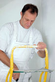 Decorator covering roller with paint — Stock Photo