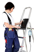 Female electrician resting laptop on rung of step-ladder — Stock Photo