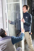 Laborers installing window — Stock Photo