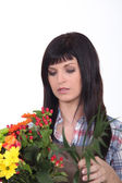Young brunette with flowers — Stock Photo