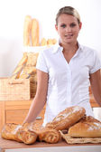 Young woman selling bread — Stock Photo