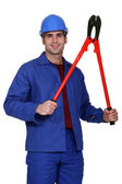 Blue collar posing with giant monkey wrench — Stock Photo