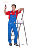 Man holding paint roller stood by step ladder — Stock Photo