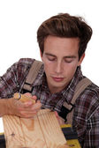 Carpenter using a chisel to sculpt wood — Stock Photo