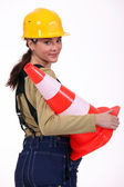 Female builder holding traffic cone — Stock Photo