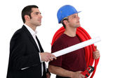 A plumber and a manager watching something — Stock Photo