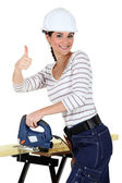 Upbeat woman using band-saw — Stock Photo