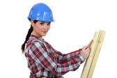 Female carpenter taking measurements of a board — Stock Photo