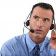Man speaking into a hands-free headset — Stock Photo #9960301