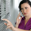 Stock Photo: Brunette businesswompeeping through blinds.