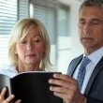Senior business couple reading through contract — Stock Photo