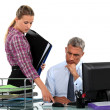 Businessman and his assistant at his desk — Stockfoto