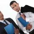 Businessmen holding folders - Stock Photo