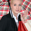 Female shopper under a brolly — Stock Photo
