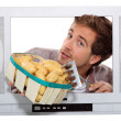 Man with new potatoes and a garden fork trapped in a television set — Stock Photo