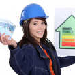 Tradeswoman holding up an energy efficiency rating chart and a wad of money — Stock Photo