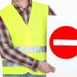 Stock Photo: A road worker holding a wrong way sign.