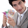 Banker holding bank notes - Stock Photo