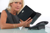 Mature businesswoman looking at her agenda — Stock Photo
