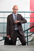 An angry businessman looking at the time — Stock Photo